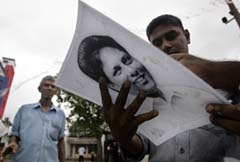 Lasantha's colleagues hold his portrait after his death. (Amarasinghe/AP)