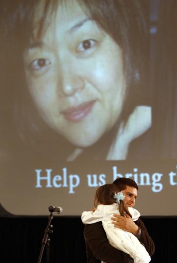 Lee's husband, Michael Saldate, holds daughter Hana during the vigil. (AP)