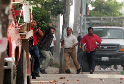 Raul Estrella, a photographer with El Universal, took these photos of gunmen, believed to be government agents, rushing toward protesters and journalists on the outskirts of Oaxaca on October 27, 2006. Brad Will, working near Estrella, was killed by gunfire that witnesses said appeared to have come from the direction of the gunmen. (El Universal/Raul Estrella)