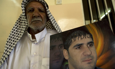 Ibrahim Jassam's photo is shown by his father in Baghdad. (Reuters/Thaier al-Sudani)