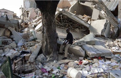 A man sits amid the rubble in Port-au-Prince. (AP)
