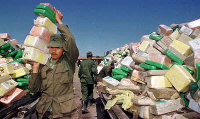A Mexican soldier carries blocks of cocaine for incineration in Matamoros. (Reuters)
