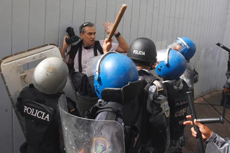 Honduran police surround AP photographer Dario Lopez-Mills as he covers protests that followed the June presidential coup. (Reuters/Oswaldo Rivas)