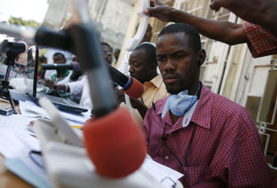 Outside their wrecked headquarters, Radio Caraibe's presenters broadcast from a makeshift studio in Port-au-Prince. (Reuters)