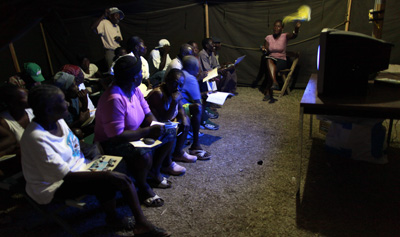 Haitian refugees watch TV in a Port-au-Prince camp. (AP)