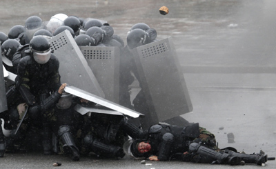 Kyrgyz police, after firing on protesters, come under attack from an angry crowd. (AP/Ivan Sekretarev)
