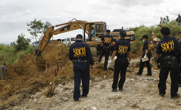 Police recover the remains of the 57 victims in Maguindanao. More than 30 were media workers. (Reuters/Erik de Castro)