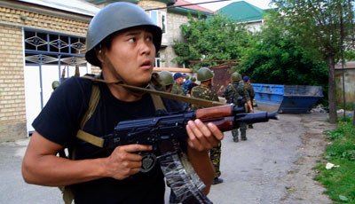 Kyrgyz Interior Ministry forces conduct house-to-house searches in the city of Osh, southern Kyrgyzstan, today. (AP)