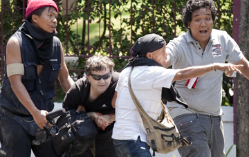 Rand is helped by protesters after being shot near Lumpini Park. (Reuters/Adrees Latif)