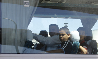 Newly freed Cuban journalists and their families on a bus taking them from Madrid Barajas Airport. (AP/Victor R. Caivano)
