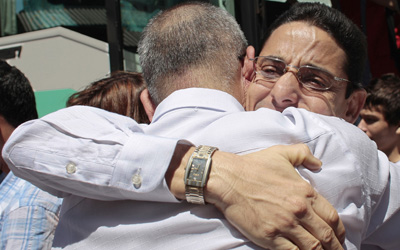 Freed journalists Normando Hernández González, right, and Omar Rodríguez Saludes hug on arrival in Madrid. (AP/Arturo Rodriguez)