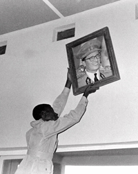 A Congolese man removes a portrait of Belgium's king in Leopoldville on July 22, 1960, at the end of colonial rule. (AP)