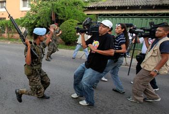 Soldados impiden a periodistas filmar cerca del palacio presidencial en Tegucigalpa luego del golpe de estado de junio de 2009. El gobierno censuró y obstaculizó el trabajo de los medios de prensa luego de que el Presidente Zelaya fuera depuesto. (AP/Esteban Felix)