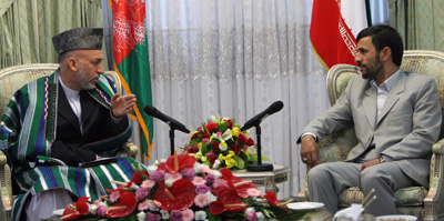 An Afghan MP is accusing President Hamid Karzai, left, of shutting down his TV station under pressure from Iran. Iranian President Mahmoud Ahmadinejad is at right. (AP/Hasan Sarbakhshian)