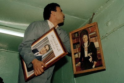 A barman in a coffeehouse in Tunis switches out the official photo of former Tunisian President Habib Bourguiba, right, to one of Zine El Abidine Ben Ali, after a bloodless coup in 1987. (AP/Laurent Rebours)