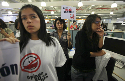 """An El Nacional journalist holds a sign that reads """"Don´t let anybody silence you"""" during a protest at the paper's newsroom in Caracas on August 18. (AP/Fernando Llano)"""