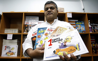 Zunar with copies of banned cartoon collections. (AP/Lai Seng Sin)