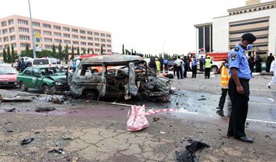 Nigerian police officer stands at scen of an exploded car bomb at Eagle Square in Abuja. (AP)