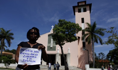 """A woman in Havana holds a sign that reads: """"My support will be eternal for freedom and justice"""" at a weekly march by members of the Cuban dissident group Ladies in White. (AP)"""