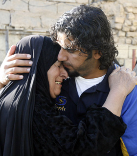 Iraqi photographer Ibrahim Jassam hugs his mother as he returns home after 17 months in U.S. custody. He was never charged with a crime. (Reuters/Thaier al-Sudani)