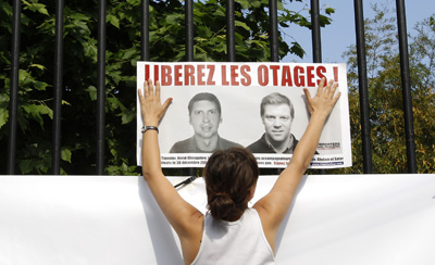A poster in the Jardin du Luxembourg in Paris shows French hostages Stephane Taponier (left) and Herve Ghesquiere. (Reuters/Benoit Tessier)