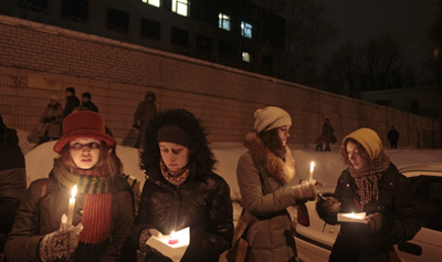 Supporters light candles today outside prison walls in Minsk for those detained in Belarus' Sunday opposition protests. (AP/Dmitry Brushko)