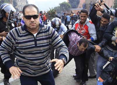 Plainclothes police chase what Reuters says is unidentified foreign journalist today in Cairo. (Reuters /Goran Tomasevic )