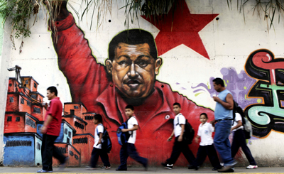 In Caracas, people pass by a mural of Chávez. (AP/Ariana Cubillos)