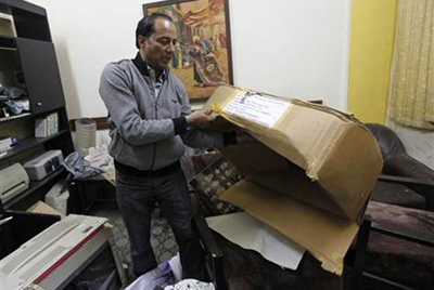 Ziad al-Ajili, head of Baghdad's Journalistic Freedoms Observatory, inspects the aftermath of a raid on his office today. (AP/Hadi Mizban)