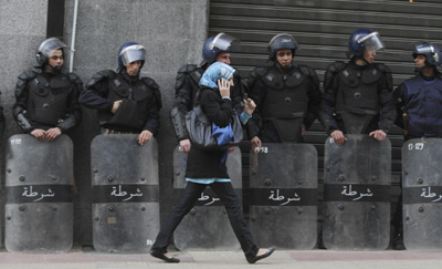 A woman walks past riot police standing guard during a demonstration in Algiers on Saturday. (Reuters/Louafi Larbi )
