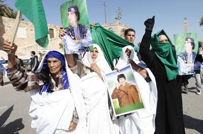 Libyan pro-government supporters hold posters of Libyan leader Muammar Qaddafi during a demonstration in Tripoli. (Reuters/Ismail Zitouny)