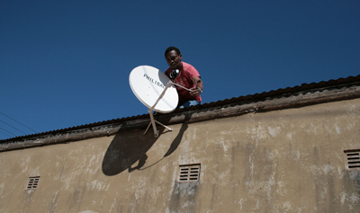 A man sets up a satellite dish in Zimbabwe, where state news is severely restricted on the ongoing protests in the Middle East, but where CNN is still accessible. (AP)