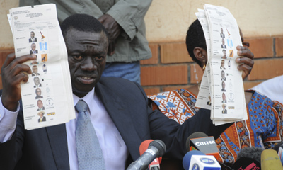 Opposition leader Kizza Besigye displays pre-marked ballot papers during a news conference Kampala. Election-rigging has been alleged in national and local polls. (AP/Stephen Wandera)