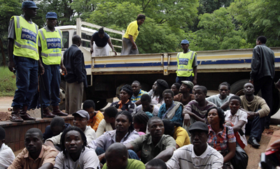 Men and women arrested for watching footage of the unrest in Egypt wait outside a Harare courthouse. (Reuters)