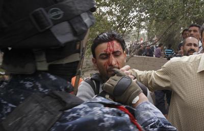 An Iraqi officer hits Al-Alam cameraman Mohammed al-Rased during a demonstration in Basra today. (AP/Nabil al-Jurani)