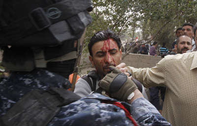 An Iraqi officer hits Al-Alam cameraman Mohammed al-Rased during a demonstration in Basra today. (AP/Nabil al-Jurani)