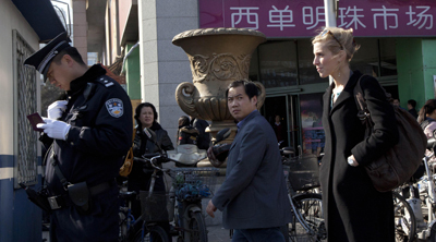 A Chinese policeman checks the identity of a foreign journalist, right, near the Xidan shopping district, a designated a demonstration site in an Internet call for protests in Beijing on Sunday. (AP)