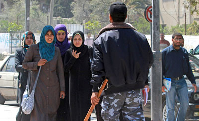 A Hamas policeman orders a group of students to disperse after they attempted to gather for a protest in Gaza City. (AP/Hatem Moussa)