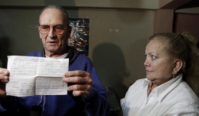 Maseda holds a document proving his release from prison next to his wife, Laura Pollán. (AP/Franklin Reyes)