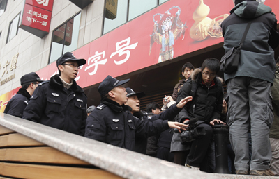 Police ask journalists to leave as they cover people gathering at a planned protest site in Beijing on Feb. 20, 2011. (AP/Andy Wong)
