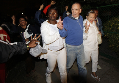 Héctor Maseda Gutiérrez walks free with his wife (right), while followed by government supporters jeering his release. (Reuters/Desmond Boylan)