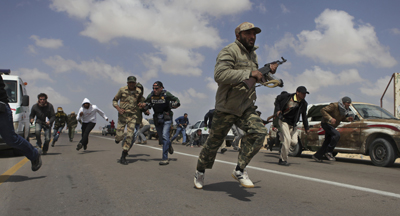 Libyan rebels and journalists run for cover as pr-Qaddafi forces shell rebel positions just outside Brega. (AP/Altaf Qadri)