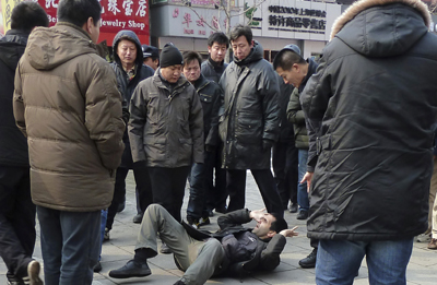 International journalists are targeted in many ways in China. Here, a foreign journalist is pushed to the ground while trying to cover a potential protest in Beijing. (Reuters)
