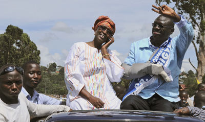 Kizza Besigye and his wife, Winnie Byanyima, wave to supporters during the procession. (AP)