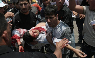 Men carry wounded photojournalist Mohammed Othman. (Mazen al-Breem/Demotix)