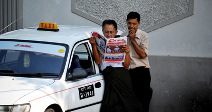 Burmese taxi drivers read a newspaper featuring a picture of newly sworn-in president Thein Sein. (AFP/Soe Than Win)