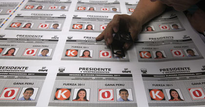 A worker inspects ballots with images of presidential candidates in Peru. Keiko Fujimori will face Ollanta Humala in a presidential runoff on June 5. (AP/Martin Mejia)