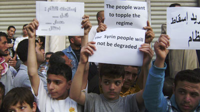 Syrians carry banners during an anti-government protest in the coastal town of Banias, Syria. (AP)