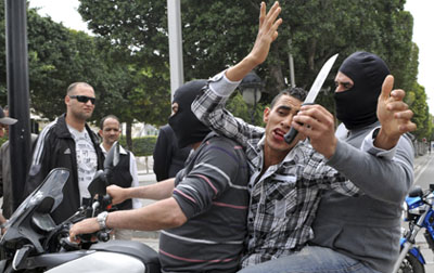 Masked plainclothes police officers take away an alleged rioter on a motorbike during clashes in Tunis. (AP/Chokri Mahjoub)