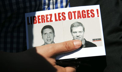 'Free the hostages!' was the rallying cry for those seeking the release of Hervé Ghesquière, left, and Stéphane Taponier. (AFP/Michel Gangne)